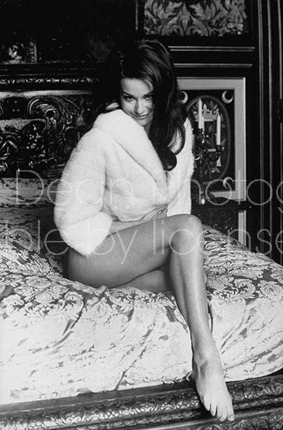 """Actress Claudine Auger clad only in a white fur jacket, posing coyly on elegant Regency bed in room at of the Chateau d'Anet, location for filming the movie """"Thunderball""""."""