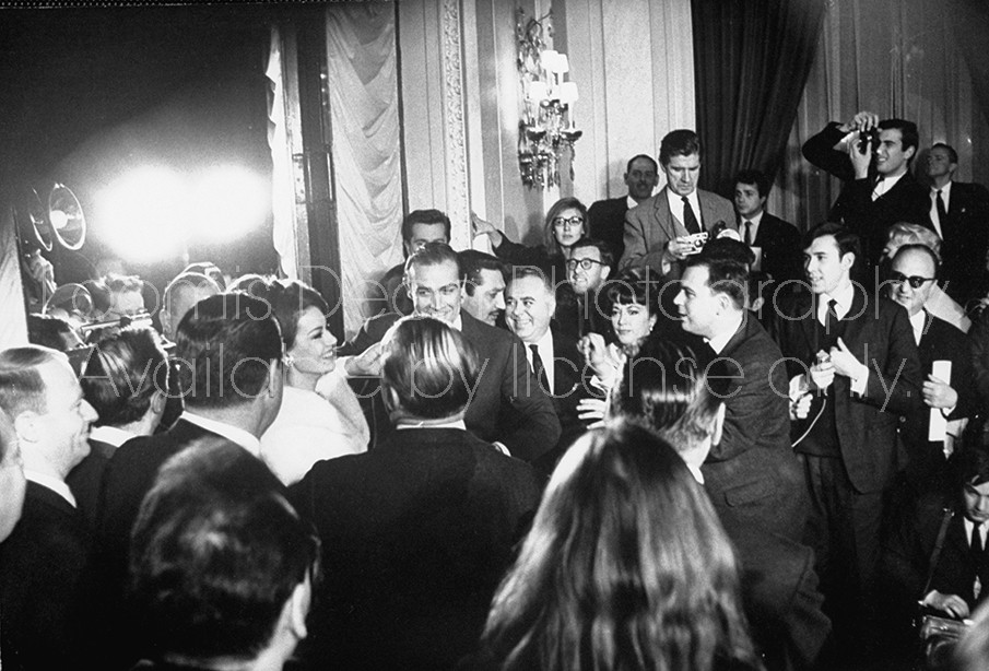 "Actress Claudine Auger in white fur w. actor Sean Connery (C) being mobbed by newsmen & photographers at reception held in the Georges Cinq Hotel after the release of their movie ""Thunderball""."