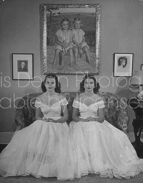 Debutantes Mary & Debbie Love posing on sofa in identical ball gowns on day of their debut into society.