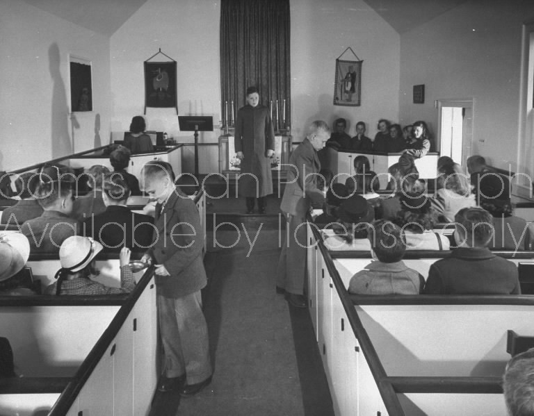 Boys taking up collection in minature church for children.