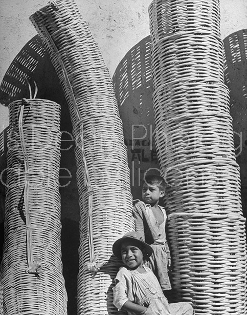 Children at a basked maker's stall in Mexico
