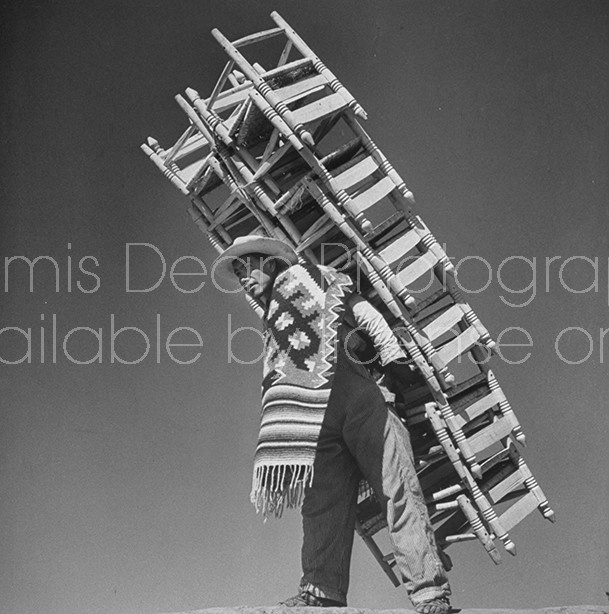 A chair vendor carrying 24 chairs to market.