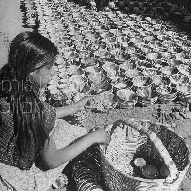 A young woman arranging her pottery for sale in the Toluca Market.