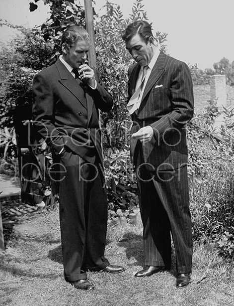 Actors Errol Flynn (L) and Anthony Quinn smoking cigarettes.