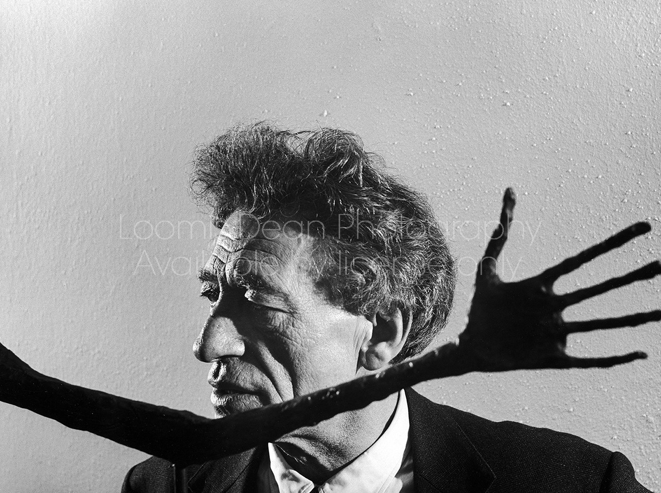 Portrait of sculptor Alberto Giacometti framed by reaching hand of one of his sculptures on display in museum.