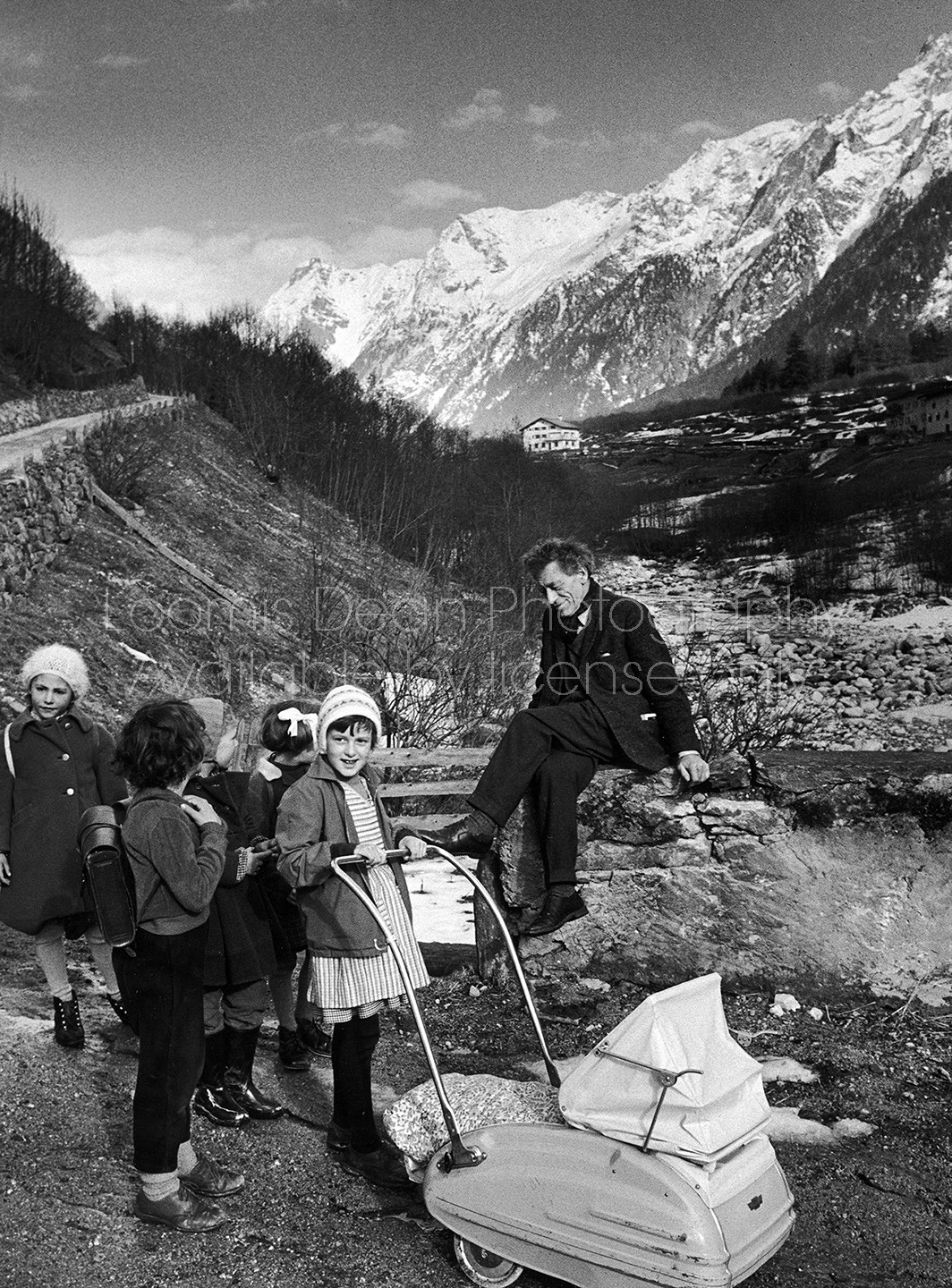 Sculptor Alberto Giacometti stopping to talk with children during a walk up the valley near his home.