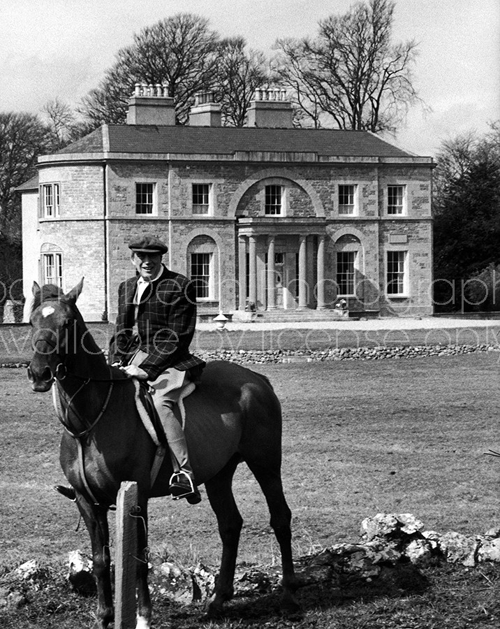 Actor/Director John Huston, sitting on top of his horse in front of his large home.