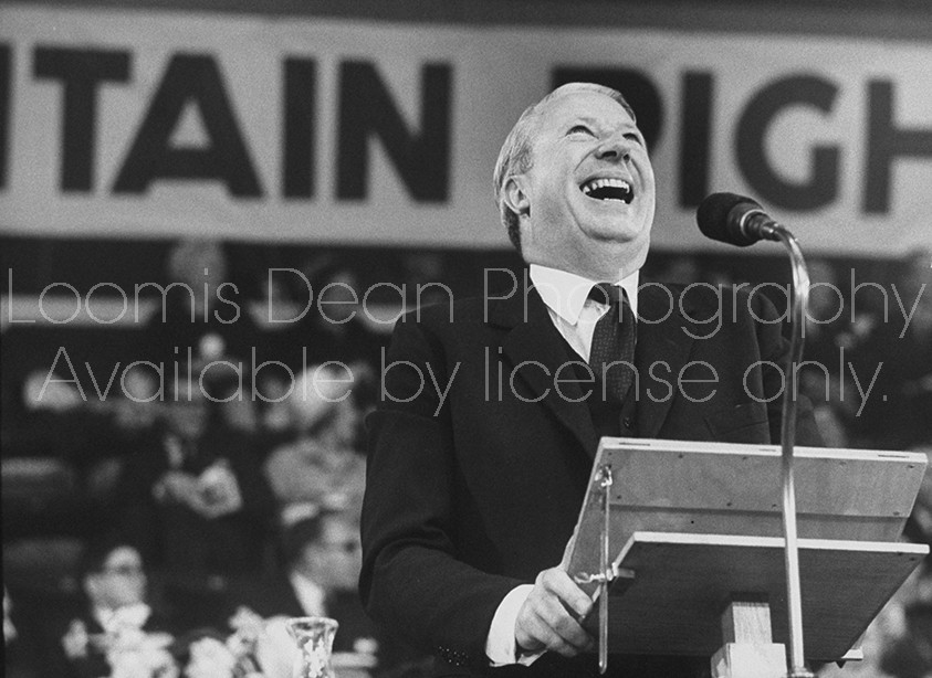 British Tory Leader Edward Health laughing at the microphone during the annual convention of the Conservative Party.