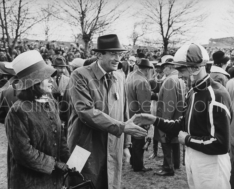 Jockey Pat Taaffe (R), and Gregory Peck and wife (L), talking at the Grand National.