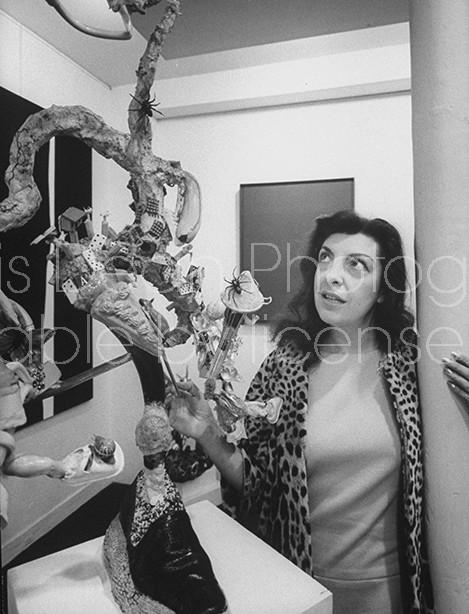 Art Dealer Iris Clert examining a Lawrence Vail sculpture at her Paris gallery.
