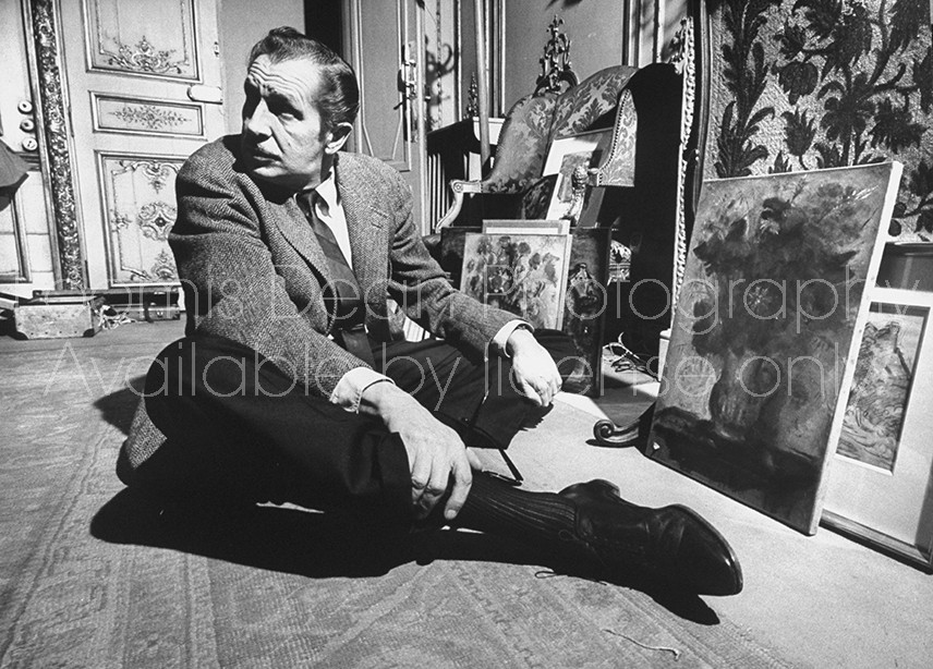 Actor Vincent Price sitting on the floor with his legs crossed in front of a few pieces of his art collection.