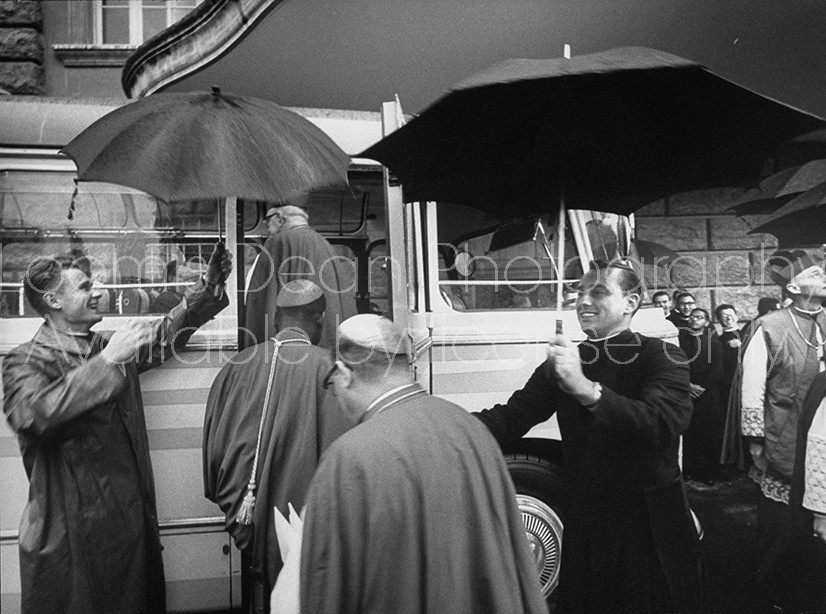 Young priests holding umbrellas over cardinals in Rome for Ecumenical Council in Rome.
