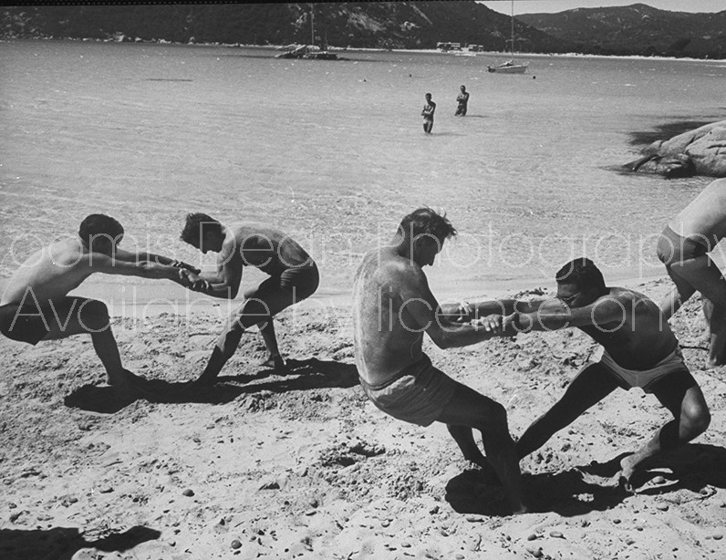 Members of French vacation Club Mediterranee doing exercises on beach.