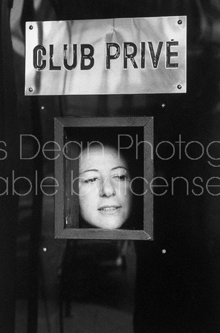 Regine, owner of chic clubs in Paris and on the Riviera, peering through door at a would-be patron.