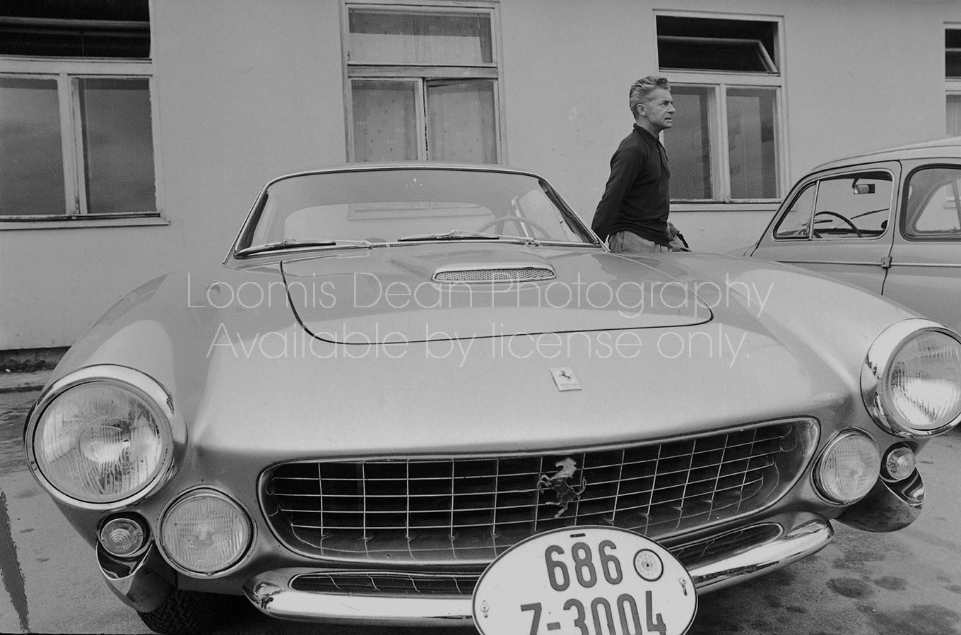 Conductor Herbert von Karajan getting out of his Ferrari at the airport, where he flies planes.  [Scanned from contact sheet.]