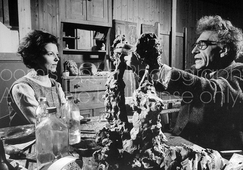 Sculptor Alberto Giacometti working on clay sculptures while his wife looks on, at his studio at home.