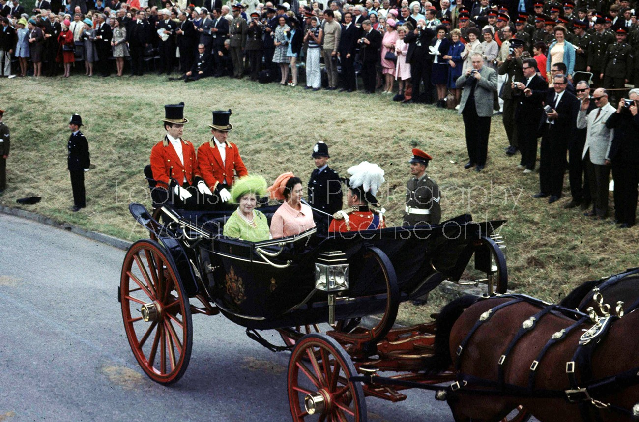 (L-R) Briatin's Queen Mother in green hat and dress and daughter Princess Margaret in peach hat and dress riding in a carriage on the occasion of Prince Charles' investiture.