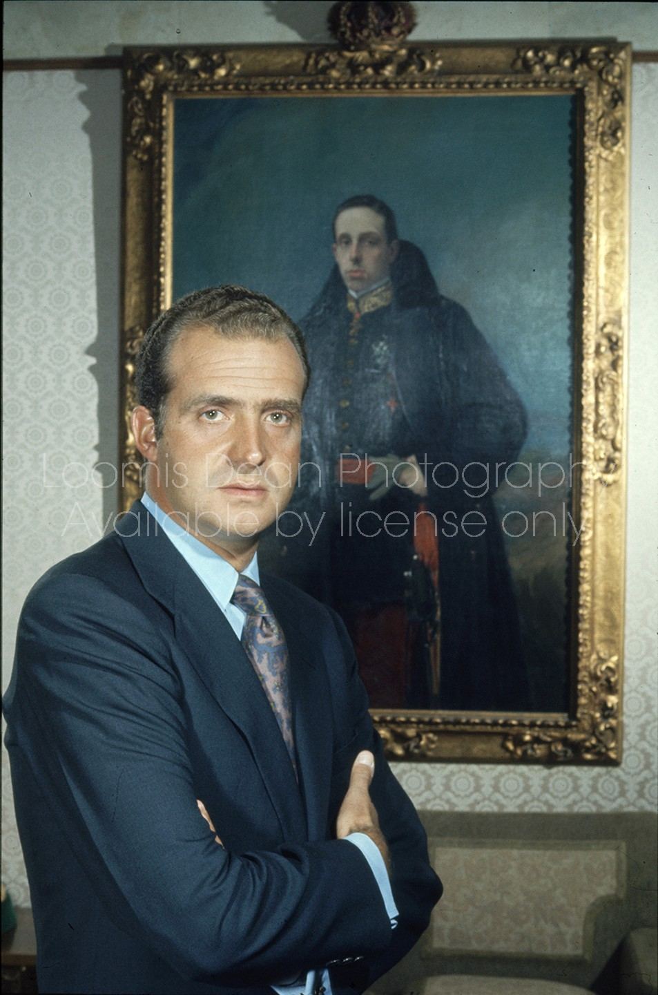 Spanish Prince Juan Carlos posing in front of portrait of his grandfather King Alphonso XIII, at home outside Madrid.