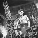A circus employed blacksmith making horseshoes.