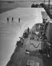 US naval personnel laying cotton sheets on the deck of a ship to preserve and seal the hull while docked in a storage depot waiting for reuse.