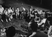 Actress Margaret Rutherford telling ghost stories to youth around a campfire.
