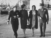"Capt. Henry Cooke with wife (L) and Lt. Col. Nathan Peevey and wife arriving from missile cruiser ""Springfield."""