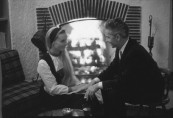 Conductor Herbert von Karajan (R) and wife Eliette, sitting in front of a fireplace; prob. Salzburg.  [Scanned from contact sheet.]