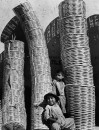Two children standing amongst stacks of baskets in Mexico.