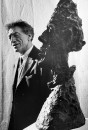 Swiss sculptor Alberto Giacometti w. one of his characteristically stylized heads, at museum.