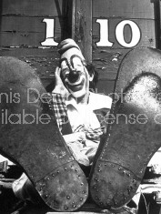 Pre-eminent clown Lou Jacobs posing in full makeup & costume w. his feet up while relaxing on tour w. the Ringling Bros. and Barnum & Bailey Circus.