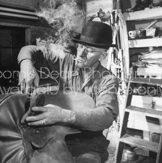 A worker for the circus fixing a saddle in his workshop.