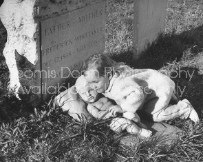 A girl posing next to a grave.