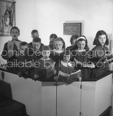 Children's chior singing during service in their minature church.