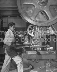 A man working at a large machine in a factory.