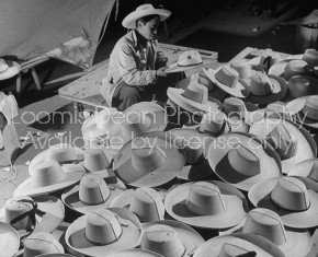 A hat vendor working among his wares at the market.