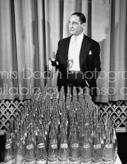 Pres. Pepsi Cola Co. Walter S. Mack Jr. standing behind empty Pepsi bottles.