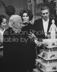 "Actor/Director Charlie Chaplin (fore) cutting cake while wife Oona, Sophia Loren and son Sydney look on during 77th birthday party on set of his film ""A Countess from Hong Kong."""