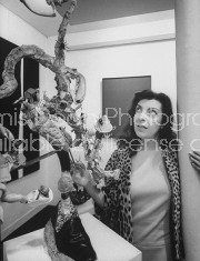Art Dealer Iris Clert examining a Lawrence Vail sculpture at her Paris gallery.