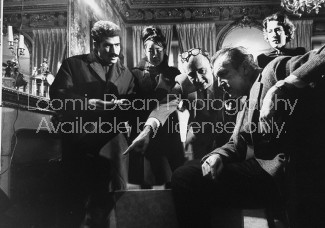 Actor Vincent Price (R) sitting in a room among several others who are all observing a particular piece of artwork.