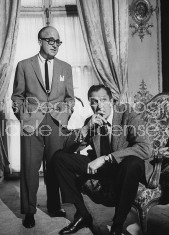 Actor Vincent Price (R) sitting forward in the chair with a cigarette in his mouth and sun glasses in his hand while another man is standing just above him with his hands resting in his trousers.