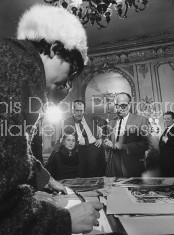 Actor Vincent Price (2nd L) observing with others in the room while a woman wearing glasses is signing some papers.
