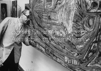 "Arnold Maremont, looking at artist Friedrich Hundertwasser's, painting ""L' Oeuf De L"" Anlien Japon Precolombien""."