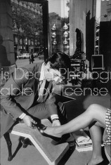 Salesman at the Pines Sane Salon in Paris France fitting a woman for a shoe.
