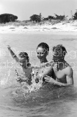 Conductor Herbert von Karajan (R) playing in the water with wife Eliette and daughter Isabelle.  [Scanned from contact sheet.]