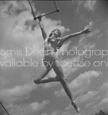 CIRCUS ACROBAT POSING FROM TRAPEZE